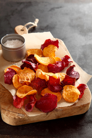 ovenbaked: Healthy vegetarian snack of crisp crunchy fried or oven-baked beetroot chips served with rock or sea salt on a wooden chopping board , close up high angle view with copyspace behind