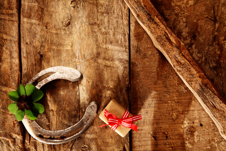 free backgrounds: Lucky horseshoe and fresh green shamrock symbolic of luck, with a small wrapped gift on an old rustic wood background with diagonal bar and copyspace for your greeting