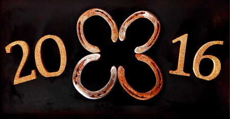 symbolical: 2016 New Year horizontal banner background with four lucky horseshoes arranged as a four-leaf clover or shamrock in the center of the date symbolising Good Luck Wishes over a dark background Stock Photo