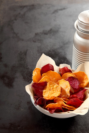 ovenbaked: Bowl of appetizing crisp beetroot and potato vegetable chips fried or oven-baked in the oven for a healthy vegetarian snack, high angle view with copyspace on a dark slate background