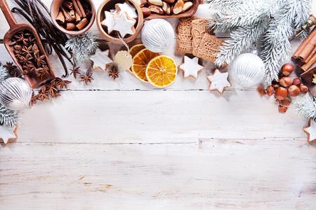 adviento: Festivo frontera de temporada de Navidad variedad de frutos secos, especias, rodajas de naranja, vainilla, galletas y decoraciones sobre un fondo de madera blanca r�stica con copyspace visto desde arriba