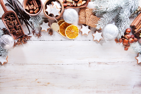 Festive seasonal Christmas border of assorted nuts, spices, orange slices, vanilla, cookies and decorations on a rustic white wood background with copyspace viewed from above Standard-Bild