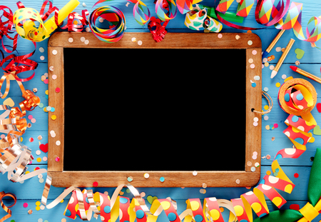 Colorful festive frame with multicolored coiled party streamers on a blue wooden background around a vintage slate with a clean chalkboard and copyspace