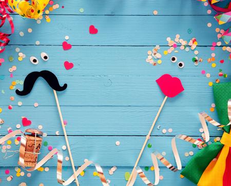 carnaval: Fun accessoires de cabine de fond de photo de fête avec un couple d'amoureux formé à partir d'une moustache et un ensemble de pulpeuses lèvres féminins rouges sur des planches de bois bleu rustique avec un cadre de banderoles de partis et noeud papillon