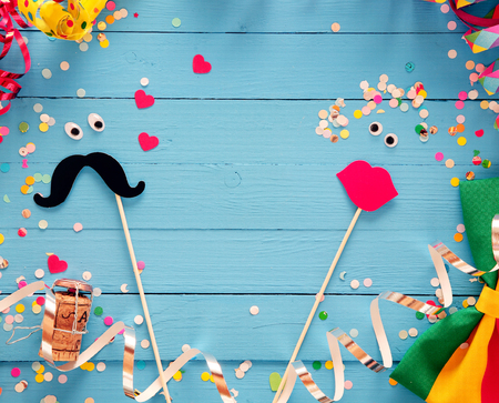 Fun photo booth accessories festive background with a loving couple formed from a mustache and set of luscious red female lips on rustic blue wooden boards with a frame of party streamers and bow tie 免版税图像