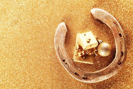herradura: Fondo de la tarjeta de Navidad de la buena suerte con una herradura de oro que encierra pequeños regalos de oro y una chuchería sobre un fondo con textura brillante con copyspace para su saludo de temporada Foto de archivo