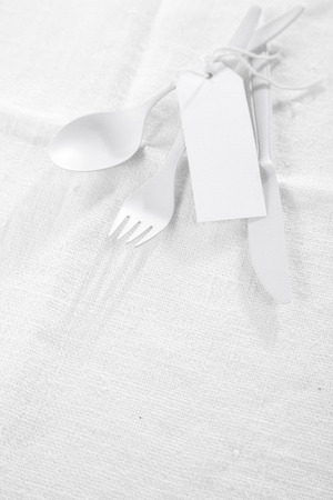tied down: Pure white monochromatic table setting with white eating utensils tied with a blank gift tag lying on a textured white tablecloth with copyspace
