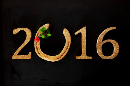 Festive 2016 New Year background with a golden date with a lucky horseshoe for the 0 decorated with a red ladybird and green shamrock symbolic of luck
