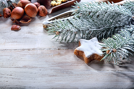 free background: Cool tone winter Christmas nuts background with hazelnuts and a star cookie amongst snow covered pine branches on a rustic white wood background with copyspace