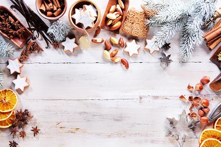 epices: Cadre de Noël ou à la frontière avec un grand assortiment d'épices, les noix, tranches d'orange et biscuits spéculoos disposés sur un fond en bois blanc avec des branches de pin et copyspace, vue de dessus