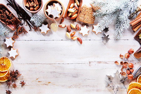 Christmas frame or border with a large assortment of spices, nuts, orange slices and speculoos biscuits arranged on a white wooden background with pine branches and copyspace, overhead view Standard-Bild