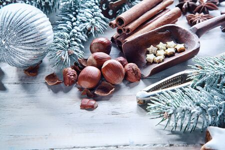 star anise christmas: Christmas nuts and spices background with hazelnuts, cinnamon, star anise and stars in a still life arrangement with a nutcracker, scoop, pine foliage and Xmas decorations
