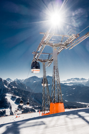 wintery day: Chair or ski lift in a resort in high snowy forested mountains with a view of a chair passing a steel tower with a sunburst behind in a sunny blue sky, travel, tourism and vacation concept