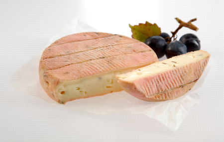 cut through: Delicious creamy soft aromatic French cheese cut through to show the ripe texture displayed with fresh black grapes over white Stock Photo