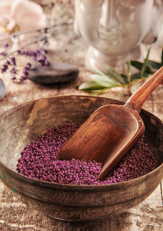 bath additive: Bath additive beads in a wooden bowl with a spoon for a bath supplements concept