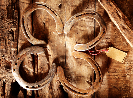 horseshoe vintage: Lucky horseshoes arranged as a shamrock symbolic of luck on an old weathered vintage rustic wood background with a small blank gift tag for your greeting, overhead view