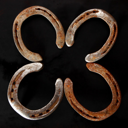 fourleafed: Four golden metallic lucky horseshoes arranged as a shamrock or four-leafed clover symbolic of luck over a dark background in square format, overhead view