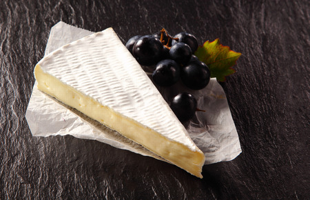wedge: Portion of ripened creamy brie cheese displayed on crumpled paper with a bunch of fresh black grapes, dark slate background with copyspace