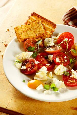 melba: Sabroso tomate cherry en rodajas y desmenuzado ensalada de queso con hierbas frescas variadas servido con crujientes tostadas de oro, opini�n de alto �ngulo de la placa Foto de archivo