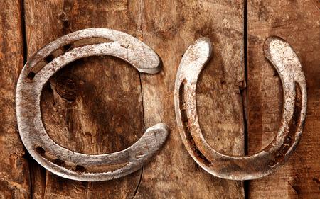 herradura: Dos viejas herraduras afortunadas tradicionales que mienten en un fondo de madera rústica con uno de lado colocados y una vertical, vista aérea Foto de archivo