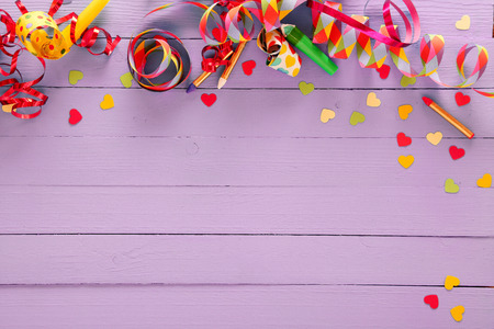parties: Colorful festive party border and background with with vibrant multicolored streamers, matches and confetti on a rustic lilac wood background with copyspace for your greeting or invitation