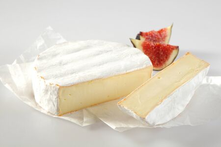 ripened: Ripened soft creamy French Camembert cheese made with full milk and originating from Normandy, served on a white paper napkin with ripe juicy purple figs