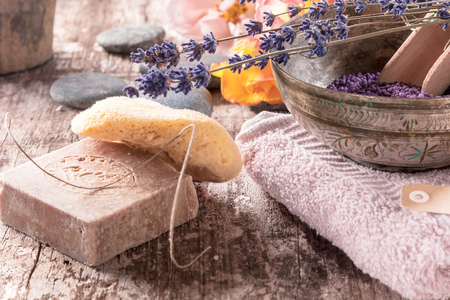 Conceptual oriantal bath supplements arrangement with bath beads, handmade soap and a greek sponge on wooden background.