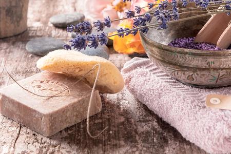 Conceptuele oriantal bad supplementen arrangement met bad kralen, handgemaakte zeep en een Griekse spons op houten achtergrond.