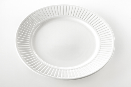 ridged: Empty round white dinner plate with a ridged rim pattern on a white background with space for food or product placement, high angle view Stock Photo