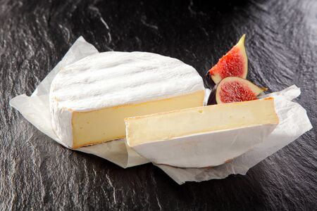 quartered: Sliced round of soft ripe creamy French Camembert cheese served with quartered juicy ripe red figs on a crumpled white paper napkin over a dark background Stock Photo