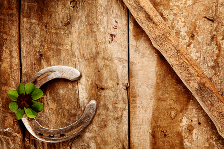 herradura: Old lucky horseshoe background with the horseshoe arranged in the corner with a green Irish shamrock for double luck on a rustic wooden background with copyspace