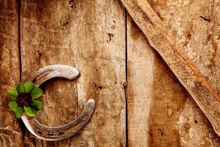 herradura: Viejo fondo de la herradura de la suerte con la herradura dispuesta en la esquina con un trébol irlandés verde para la suerte doble sobre un fondo de madera rústica con copyspace Foto de archivo