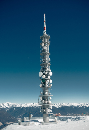 wintery day: Communications tower full of antennae and satellite dishes on a high snowy mountain summit with a view of distant snow-capped mountain ranges