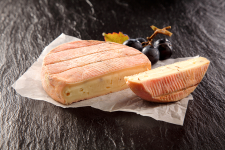 Round of creamy soft aromatic French cheese sliced in half to show the texture served on rumpled paper with fresh black grapes on a slate counter top Фото со стока