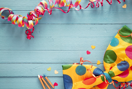 wooden boards: Festive party background with colorful streamers and a bright polka dot bow tie on rustic blue wooden boards with copyspace and scattered heart confetti