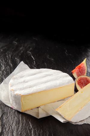 quartered: Gourmet ripe soft French Camembert cheese sliced through to show the creamy center served with quartered fresh juicy figs on a dark background with copyspace