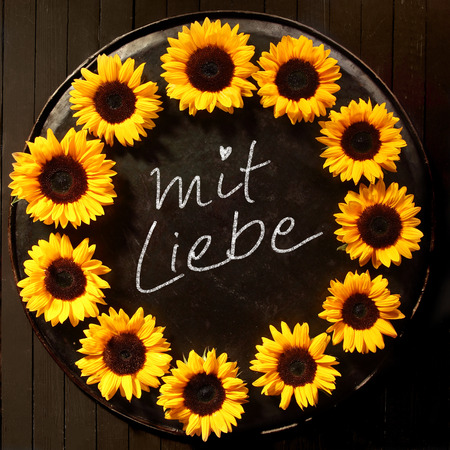 arrangment: Mit Liebe - With Love - sunflower frame with a circular arrangment of bright yellow sunflowers on a vintage tray with handwritten text - Mit Liebe - in the center over a black background