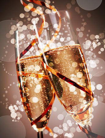 Two festive flutes of bubbly champagne with sparkling bokeh wound round with a gold party streamer conceptual of a wedding, New Year or anniversary celebration