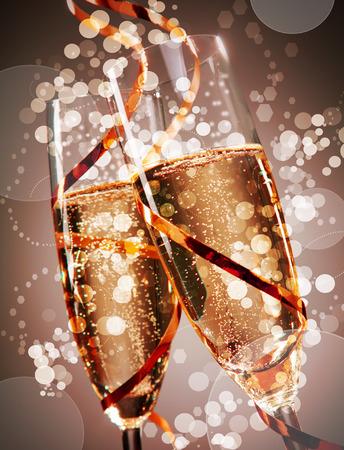 anniversario matrimonio: Due flauti di festa di champagne frizzante con bokeh scintillante avvolte attorno con una banderuola oro partito concettuale di un matrimonio, Capodanno o anniversario