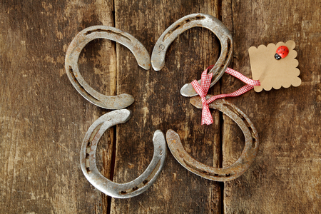 fourleafed: Four traditional lucky horseshoes arranged as a shamrock or four-leafed clover with a blank gift tag for your greeting or message on rustic wood