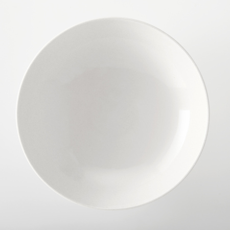 Empty plain white generic bowl viewed close up overhead with space for placement of food on a white background Zdjęcie Seryjne