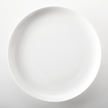 high angle view: Empty plain white round generic dinner plate with place for placement of food or a recipe viewed close up overhead over a white background in square format Stock Photo