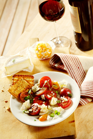 accompaniment: Side dish of fresh cheese salad with cherry tomatoes and fresh herbs served with red wine as a healthy accompaniment to a meal