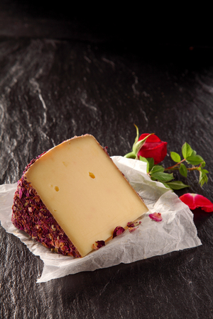 formal dinner: Aromatic gourmet cheese with a dried rose petal covering served on a slate slab on crumpled paper with a red rose decoration as an appetizer to a formal dinner, with copyspace