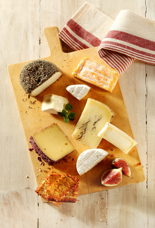 cheeseboard: Assortment of soft and semi-hard cheeses on a cheeseboard with sliced fresh figs and toast for a gourmet appetizer to a meal, view from above