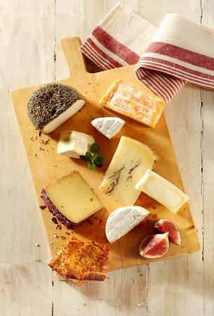 tabla de quesos: Surtido de quesos blandos y semiduros en una tabla de quesos con higos frescos en rodajas y tostadas para un aperitivo de gourmet a una comida, ver desde arriba