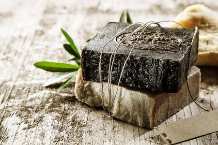 aromatic: Two bars of healthy aromatic soap made with plant extracts and essential oils for a relaxing spa treatment or bath time tied with string on a rustic wood background