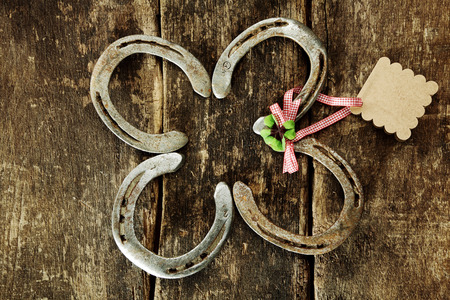fourleafed: Four lucky horseshoes arranged as a four-leafed clover with a green Irish shamrock tied with a blank gift tag on a rustic wood background , overhead view