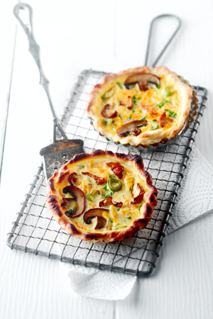 Homemade savory autumn quiche with fresh seasonal mushrooms in a crisp pastry base standing on a wire rack with a vintage spatula Stock Photo