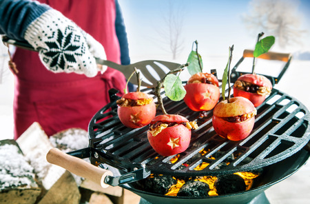 barbeque: Hand in a knitted mitten cooking stuffed apples with nuts and raisins outdoors over the hot coals of a winter barbecue with a spatula